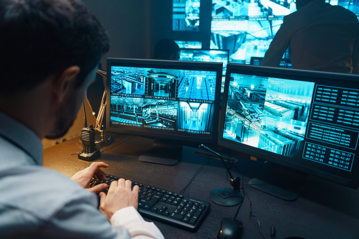 Private investigator watching video monitoring surveillance security system.