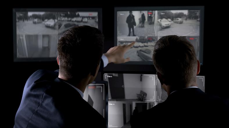 private investigator viewing surveillance monitors