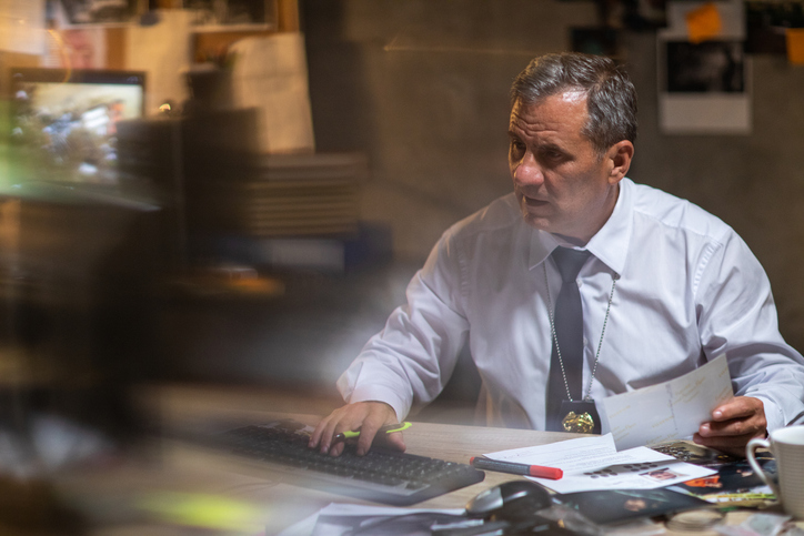 A government investigator with one hand on the keyboard and one hand on a document